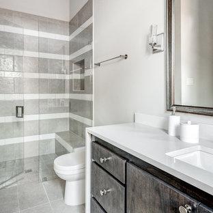 Photo of a large mediterranean ensuite bathroom in Dallas with shaker cabinets, white cabinets, a walk-in shower, a two-piece toilet, grey tiles, porcelain tiles, white walls, porcelain flooring, a submerged sink, engineered stone worktops, grey floors, a hinged door and white worktops.