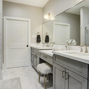 Inspiration pour une grande salle de bain design avec un placard à porte shaker, des portes de placard grises, un mur gris, un lavabo encastré, une cabine de douche à porte coulissante et un plan de toilette blanc.
