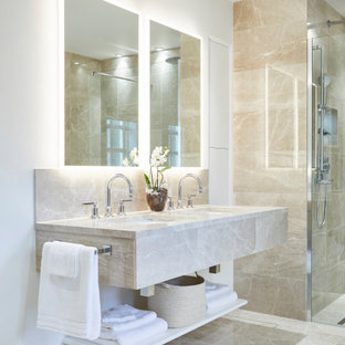 Inspiration for a large contemporary ensuite bathroom in Cardiff with beige cabinets, beige tiles, white walls, a submerged sink, grey floors, beige worktops, double sinks, a floating vanity unit, a walk-in shower, a wall mounted toilet, marble flooring, marble worktops and an open shower.
