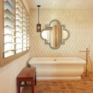 Foto di una stanza da bagno padronale costiera di medie dimensioni con vasca freestanding, piastrelle beige, piastrelle in ceramica, pareti beige, pavimento in terracotta e pavimento arancione