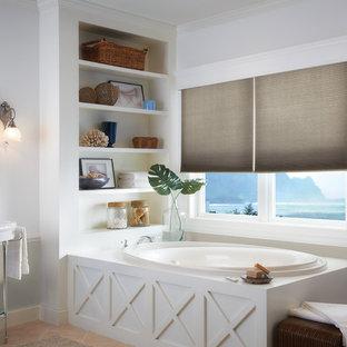 Ispirazione per una stanza da bagno padronale classica di medie dimensioni con vasca da incasso, pareti multicolore, pavimento in gres porcellanato, lavabo a consolle e pavimento arancione