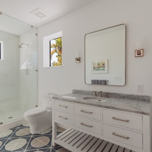 Alcove shower - mid-sized coastal 3/4 multicolored floor alcove shower idea in Miami with furniture-like cabinets, white cabinets, a two-piece toilet, white walls, an undermount sink, a hinged shower door and gray countertops