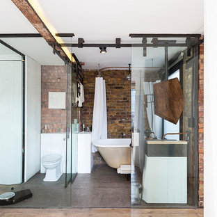 Small industrial bathroom in London with white cabinets, a freestanding bath, a one-piece toilet and a shower curtain.