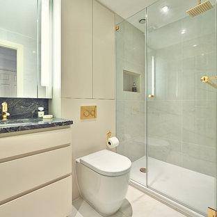 Modelo de cuarto de baño con ducha, contemporáneo, con lavabo bajoencimera, armarios con paneles lisos, puertas de armario beige, ducha empotrada, sanitario de pared y baldosas y/o azulejos grises