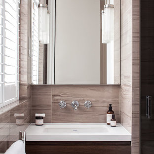 This is an example of a contemporary bathroom in London with flat-panel cabinets, dark wood cabinets, beige walls and a submerged sink.