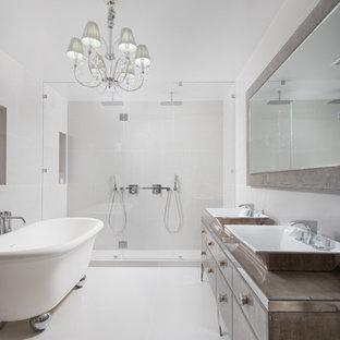 Стильный дизайн: главная ванная комната среднего размера в стиле модернизм с фасадами островного типа, фасадами цвета дерева среднего тона, отдельно стоящей ванной, двойным душем, унитазом-моноблоком, белой плиткой, керамической плиткой, белыми стенами, полом из керамической плитки, настольной раковиной, стеклянной столешницей, бежевым полом, душем с распашными дверями и бирюзовой столешницей - последний тренд