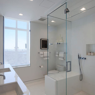 Inspiration for a large contemporary master white tile and glass sheet doorless shower remodel in New York with flat-panel cabinets, white cabinets, an undermount sink, glass countertops, a one-piece toilet and white walls