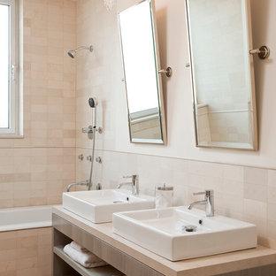 Modelo de cuarto de baño infantil, actual, de tamaño medio, con lavabo sobreencimera, armarios abiertos, puertas de armario grises, bañera encastrada, combinación de ducha y bañera, sanitario de pared, baldosas y/o azulejos beige, baldosas y/o azulejos de piedra caliza, paredes beige, suelo con mosaicos de baldosas, encimera de piedra caliza y encimeras beige