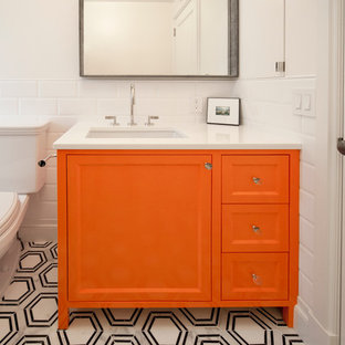 Photo of a small classic shower room in New York with recessed-panel cabinets, orange cabinets, an alcove bath, an alcove shower, a two-piece toilet, white tiles, ceramic tiles, white walls, marble flooring, a submerged sink, quartz worktops, grey floors and a shower curtain.