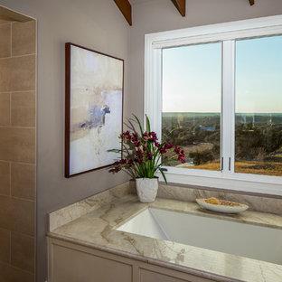 オースティンのトラディショナルスタイルのおしゃれなマスターバスルーム (アンダーマウント型浴槽、茶色いタイル、茶色い壁、磁器タイルの床、珪岩の洗面台) の写真