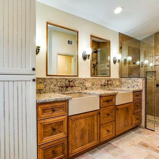 Идея дизайна: большая главная ванная комната в средиземноморском стиле с фасадами с декоративным кантом, коричневыми фасадами, ванной на ножках, душем без бортиков, унитазом-моноблоком, бежевой плиткой, плиткой из листового камня, бежевыми стенами, полом из керамической плитки, врезной раковиной, столешницей из искусственного кварца, разноцветным полом и душем с распашными дверями