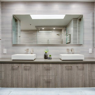 Inspiration for a contemporary master gray floor and double-sink alcove shower remodel in Los Angeles with flat-panel cabinets, medium tone wood cabinets, a vessel sink, gray countertops and a floating vanity