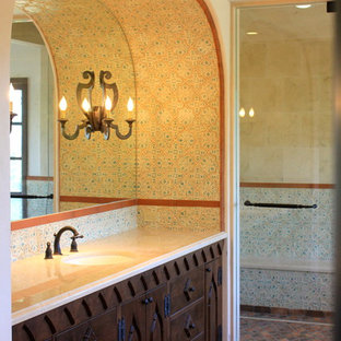 This is an example of an expansive mediterranean ensuite bathroom in San Diego with a submerged sink, recessed-panel cabinets, dark wood cabinets, marble worktops, a freestanding bath, a double shower, a two-piece toilet, multi-coloured tiles, terracotta tiles, white walls and concrete flooring.