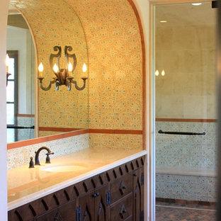 Geräumiges Mediterranes Badezimmer En Suite mit Unterbauwaschbecken, Schrankfronten mit vertiefter Füllung, dunklen Holzschränken, Marmor-Waschbecken/Waschtisch, freistehender Badewanne, Doppeldusche, Wandtoilette mit Spülkasten, farbigen Fliesen, Terrakottafliesen, weißer Wandfarbe und Betonboden in San Diego