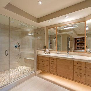 Idéer för att renovera ett funkis beige beige badrum, med släta luckor, skåp i ljust trä, en dusch i en alkov, beige kakel, beige väggar, ett undermonterad handfat, beiget golv och dusch med gångjärnsdörr