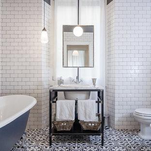 Ejemplo de cuarto de baño industrial con bañera con patas, baldosas y/o azulejos blancos, baldosas y/o azulejos de cemento, lavabo tipo consola, sanitario de una pieza, armarios con paneles empotrados y puertas de armario blancas
