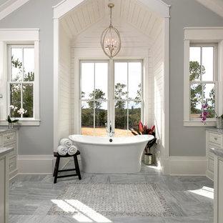 Immagine di una stanza da bagno padronale costiera con ante con riquadro incassato, ante grigie, vasca freestanding e pareti grigie