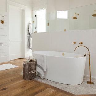 Idee per una stanza da bagno padronale stile marinaro con lavabo a colonna, vasca freestanding, doccia doppia, pareti bianche e pavimento in legno massello medio