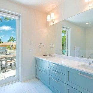 クリーブランドの大きいコンテンポラリースタイルのおしゃれなマスターバスルーム (シェーカースタイル扉のキャビネット、ターコイズのキャビネット、アルコーブ型シャワー、分離型トイレ、白い壁、セラミックタイルの床、アンダーカウンター洗面器、珪岩の洗面台、白い床、開き戸のシャワー、白い洗面カウンター) の写真