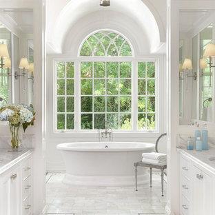 Idee per una grande stanza da bagno padronale classica con consolle stile comò, ante bianche, vasca freestanding, pareti bianche, pavimento in marmo, lavabo sottopiano, top in marmo, pavimento bianco e top bianco