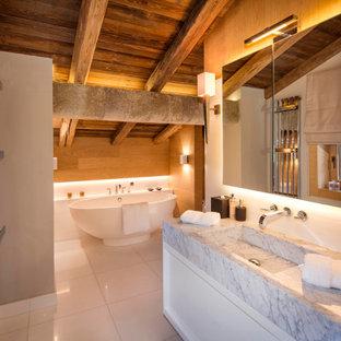 ロンドンのラスティックスタイルのおしゃれな浴室 (白いキャビネット、置き型浴槽、大理石の洗面台、洗面台1つ、フラットパネル扉のキャビネット、白い壁、一体型シンク、白い床、グレーの洗面カウンター、フローティング洗面台、表し梁、三角天井、板張り天井) の写真
