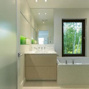 Imagen de cuarto de baño principal, actual, pequeño, con armarios con paneles lisos, puertas de armario de madera clara, bañera esquinera, ducha abierta, sanitario de pared, baldosas y/o azulejos blancos, baldosas y/o azulejos en mosaico, paredes blancas, suelo de baldosas de porcelana, lavabo bajoencimera y encimera de mármol