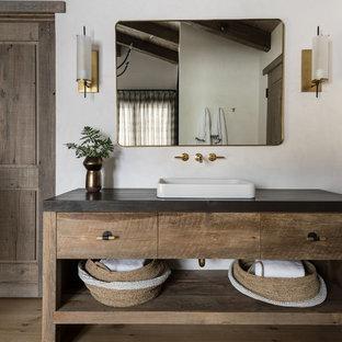 他の地域のラスティックスタイルのおしゃれな浴室 (家具調キャビネット、中間色木目調キャビネット、白い壁、無垢フローリング、ベッセル式洗面器、茶色い床、黒い洗面カウンター) の写真