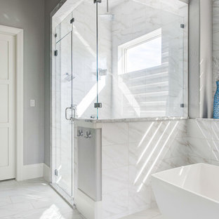 Inspiration for a large transitional master bathroom in Dallas with raised-panel cabinets, turquoise cabinets, a freestanding tub, a corner shower, a two-piece toilet, gray tile, marble, grey walls, marble floors, an undermount sink, marble benchtops, grey floor and a hinged shower door.