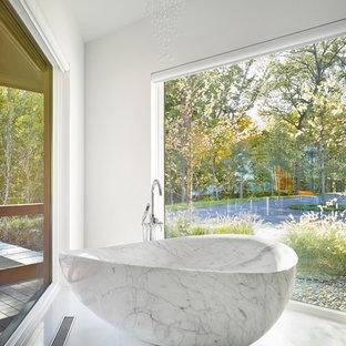 Modern inredning av ett badrum, med ett fristående badkar, vita väggar och vitt golv