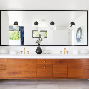 Example of a mid-sized trendy master white tile and ceramic tile gray floor bathroom design in Los Angeles with flat-panel cabinets, medium tone wood cabinets, a one-piece toilet, white walls, an undermount sink, solid surface countertops and white countertops