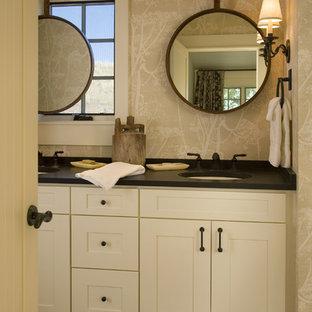 Modelo de cuarto de baño tradicional, de tamaño medio, con lavabo bajoencimera, armarios con paneles empotrados, puertas de armario beige, suelo de baldosas tipo guijarro, baldosas y/o azulejos grises, suelo de baldosas tipo guijarro y paredes beige