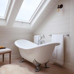 Cette photo montre une salle de bain chic avec une baignoire sur pieds, un mur blanc, un sol en bois clair et un sol beige.