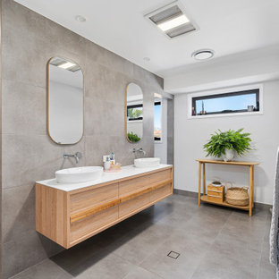 Photo of a large contemporary master bathroom in Gold Coast - Tweed with flat-panel cabinets, light wood cabinets, an alcove shower, gray tile, porcelain tile, grey walls, porcelain floors, a vessel sink, solid surface benchtops, grey floor, an open shower and white benchtops.