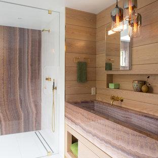 Réalisation d'une grand salle de bain principale minimaliste avec une grande vasque, un placard à porte plane, des portes de placard en bois clair, un plan de toilette en onyx, une douche à l'italienne, un WC à poser, un carrelage blanc, des carreaux de céramique, un mur multicolore et un sol en carrelage de porcelaine.