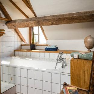 Idee per una stanza da bagno padronale di medie dimensioni con vasca da incasso, vasca/doccia, piastrelle bianche, piastrelle in ceramica, pareti bianche, pavimento in terracotta, lavabo sospeso e pavimento arancione