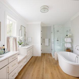 Idee per una stanza da bagno padronale chic con vasca freestanding, doccia ad angolo, lavabo sottopiano, porta doccia a battente, top bianco, ante con riquadro incassato, ante bianche, piastrelle bianche, pareti grigie, pavimento in legno massello medio e pavimento marrone