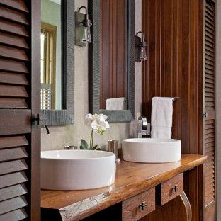 Ejemplo de cuarto de baño rural con armarios tipo mueble, puertas de armario de madera oscura, lavabo sobreencimera, encimera de madera, suelo gris y encimeras marrones