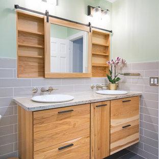 Exempel på ett mellanstort modernt beige beige badrum, med släta luckor, skåp i ljust trä, ett badkar i en alkov, en dusch/badkar-kombination, en toalettstol med separat cisternkåpa, beige kakel, keramikplattor, gröna väggar, klinkergolv i porslin, ett nedsänkt handfat, granitbänkskiva, grått golv och dusch med skjutdörr