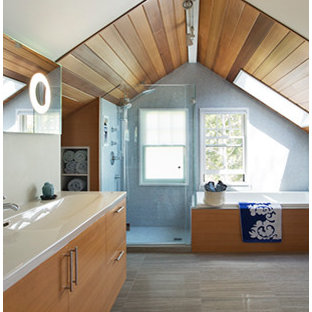 Example of a mid-sized 1960s 3/4 blue tile and mosaic tile medium tone wood floor bathroom design in Boston with a trough sink, flat-panel cabinets, medium tone wood cabinets, solid surface countertops and a one-piece toilet