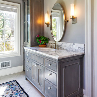 Example of a classic master marble floor freestanding bathtub design in New York with marble countertops, gray cabinets, beaded inset cabinets, gray walls and white countertops
