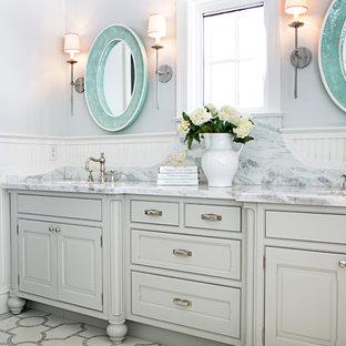 Foto di una stanza da bagno tradizionale con lavabo sottopiano, ante grigie, pareti bianche e ante con bugna sagomata