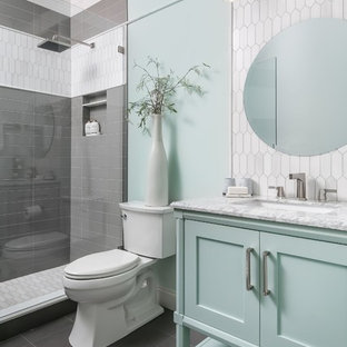 Example of a beach style 3/4 gray tile and white tile gray floor bathroom design in Atlanta with furniture-like cabinets, green cabinets, a two-piece toilet, green walls, an undermount sink and white countertops