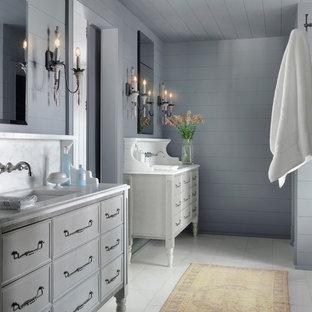 Exemple d'une salle de bain principale romantique avec un placard en trompe-l'oeil, des portes de placard grises, un mur gris, un lavabo encastré, un sol blanc et un plan de toilette blanc.