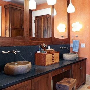 Foto di una grande stanza da bagno padronale rustica con lavabo a bacinella, top in saponaria, pareti arancioni, ante con riquadro incassato, doccia alcova, porta doccia a battente e top blu