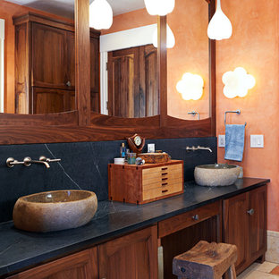 This is an example of a large country master bathroom in Other with a vessel sink, soapstone benchtops, orange walls, recessed-panel cabinets, an alcove shower, a hinged shower door and blue benchtops.