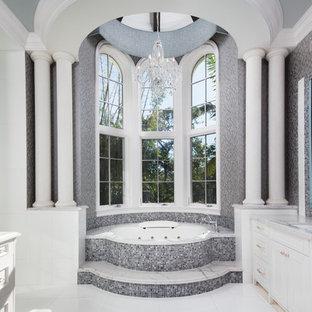 Idee per una stanza da bagno padronale chic con ante con riquadro incassato, ante bianche, vasca idromassaggio, piastrelle grigie, piastrelle a mosaico, pareti grigie, lavabo sottopiano e pavimento bianco