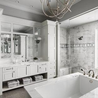 Immagine di una stanza da bagno padronale chic con ante con riquadro incassato, ante bianche, vasca sottopiano, zona vasca/doccia separata, piastrelle grigie, pareti grigie, lavabo da incasso, pavimento grigio e porta doccia a battente