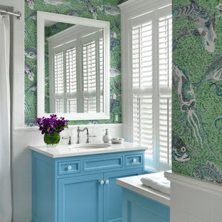 Foto di una stanza da bagno con doccia costiera di medie dimensioni con lavabo sottopiano, ante con riquadro incassato, ante blu, piastrelle bianche, piastrelle a mosaico, doccia alcova, pavimento in gres porcellanato, top in quarzo composito, pareti multicolore e top bianco
