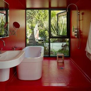 Idée de décoration pour une salle de bain principale minimaliste de taille moyenne avec une baignoire indépendante, un lavabo suspendu, un mur rouge, un placard à porte plane, une douche ouverte et un sol rouge.