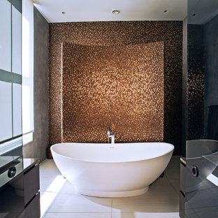 This is an example of a contemporary bathroom in London with flat-panel cabinets, dark wood cabinets, a freestanding bath, brown tiles, mosaic tiles, grey walls, beige floors and brown worktops.